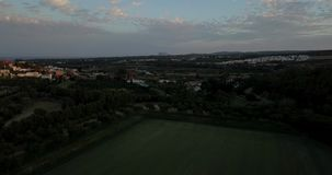 Aerial flight over hills and polo field at sunset. Aerial drone footage over hills and polo fields at sunset, camera moving backwards ascending stock footage