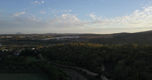 Aerial flight over hills and polo field at sunset. Aerial drone footage over hills and polo fields at sunset, camera panning left stock video footage
