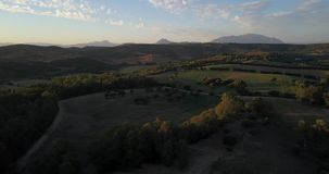 Aerial flight over hills and polo field at sunset. Aerial drone footage over hills and polo fields at sunset, camera panning right stock footage