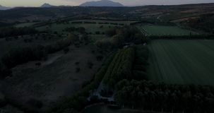Aerial flight over hills and polo field at sunset. Aerial drone footage over hills and polo fields at sunset, camera tilting down and moving backwards stock footage