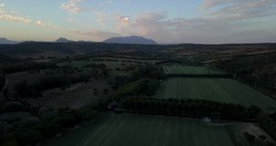 Aerial flight over hills and polo field at sunset. Aerial drone footage over hills and polo fields at sunset, camera tilting up stock video