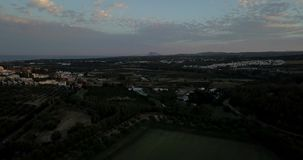 Aerial flight over hills and polo field at sunset. Aerial drone footage over hills and polo fields at sunset, camera tilting up and moving forward stock video