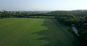 Aerial flight over hills and polo fields at sunset. Aerial drone footage over hills and polo fields at sunset, camera moving forward. Mavic Pro drone/quadcopter stock footage