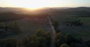 Aerial flight over hills at sunset. Aerial drone footage over hills at sunset with camera moving up stock footage