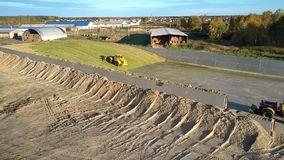Aerial flight over huge silage pits with operating machinery. Pictorial aerial flight over huge silage pits with operating machinery near livestock complex on stock footage