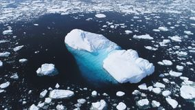 Aerial flight over iceberg among Antarctica ocean. Climate Change in Winter Ocean Scape. Drone Shot Of Huge Ice Glacier, Snow Pieces Floating In Clear Ocean stock footage