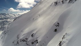 AERIAL: Flight over mountain covered with snow