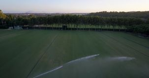 Aerial flight over polo field with large sprinklers watering the grass. Aerial drone footage over polo fields at sunset, camera moving forward and up stock footage