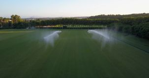 Aerial flight over polo field with large sprinklers watering the grass, forming a rainbow. Aerial drone footage over polo fields at sunset, camera moving up and stock video footage