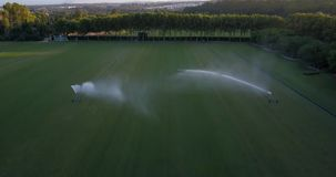 Aerial flight over polo field with large sprinklers watering the grass, forming a rainbow. Aerial drone footage over polo fields at sunset, camera moving forward stock footage