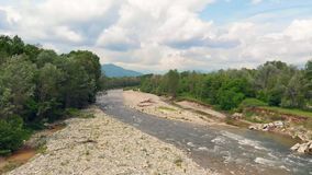 Aerial: flight over river flowing between woodland with mountain background and cloudscape, Turin, Italy.  stock footage