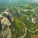 Aerial flight over roads and moody landscape in Meteora royalty free stock image