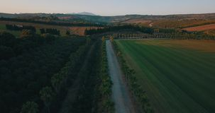 Aerial flight over rural road and hills at sunset stock video footage