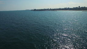 Aerial flight over sailboat at Black Sea, city coastline on the background stock video