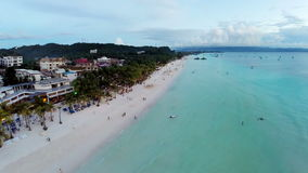 Aerial flight over sandy beach, waves and tourists stock footage