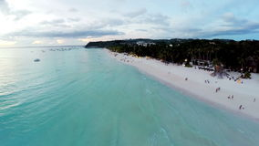 Aerial flight over sandy beach, waves and tourists stock video