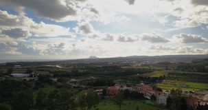 Aerial flight over small Spanish village. Aerial drone footage over small Spanish village with cloudy and overcast sky and smooth upwards movement. Gibraltar stock video footage
