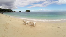 Aerial flight : two Empty  chair  on a beach  by the ocean stock video footage