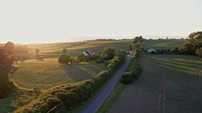 Aerial flight upwards over green fields and sunset in Germany stock video
