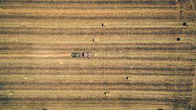 Aerial flight view of a cube baler tractor discharges a fresh wheat bale during harvesting Stock Photo