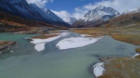 aerial Fluss, der durch schneebedecktes Gebirgstal läuft stock footage