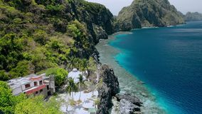 Aerial fly over Matinloc Shrine along the coastline. El Nido, Palawan, Philippines. Bizarre limestone mountain rocks and. Coral reef und crystal clear blue stock footage