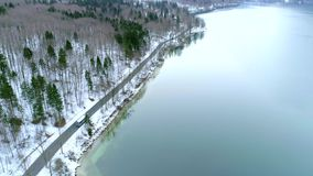 Aerial fly over road with a bus at the Bohinj lake. In winter stock footage