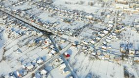 Aerial fly over snowy village tilt shift miniature. Aerial survay over snowy crossroad in the village. Tilt shift miniature stock video