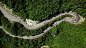 Aerial fly under curved winding road trough the mountains stock video