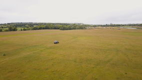 Aerial. Flying above the suv car driving fast offroad through rural countryside stock video footage