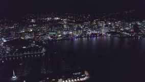 Aerial, Flying Into City At Night, Skyline Illuminated. High above city streets, illuminated streets and buildings light up at night stock video footage