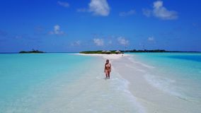 Aerial flying drone view of Maldives white sandy beach happy 1 person young beautiful young woman walking on. Sunny tropical paradise island with aqua blue sky stock images