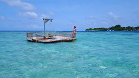 P02020 Aerial flying drone view of Maldives white sandy beach happy young woman relaxing on floating pontoon jetty Royalty Free Stock Images