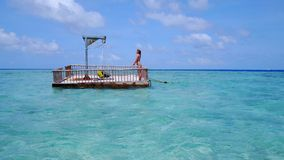 P02016 Aerial flying drone view of Maldives white sandy beach happy young woman relaxing on floating pontoon jetty Royalty Free Stock Photos