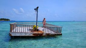 P02011 Aerial flying drone view of Maldives white sandy beach happy young woman relaxing on floating pontoon jetty Stock Photography