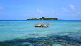 P02017 Aerial flying drone view of Maldives white sandy beach happy young woman relaxing on floating pontoon jetty Stock Image
