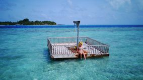 P02021 Aerial flying drone view of Maldives white sandy beach happy young woman relaxing on floating pontoon jetty Stock Images