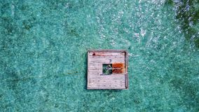 P02001 Aerial flying drone view of Maldives white sandy beach happy young woman relaxing on floating pontoon jetty Royalty Free Stock Images