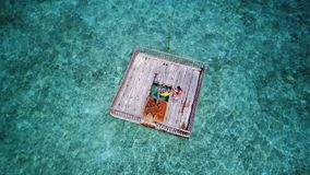 P02004 Aerial flying drone view of Maldives white sandy beach happy young woman relaxing on floating pontoon jetty Stock Photo