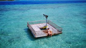 P02015 Aerial flying drone view of Maldives white sandy beach happy young woman relaxing on floating pontoon jetty Royalty Free Stock Photography