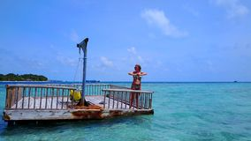 P02014 Aerial flying drone view of Maldives white sandy beach happy young woman relaxing on floating pontoon jetty Royalty Free Stock Image
