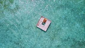 P02023 Aerial flying drone view of Maldives white sandy beach happy young woman relaxing on floating pontoon jetty Royalty Free Stock Photo