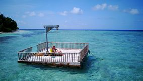 P02019 Aerial flying drone view of Maldives white sandy beach happy young woman relaxing on floating pontoon jetty Stock Photos