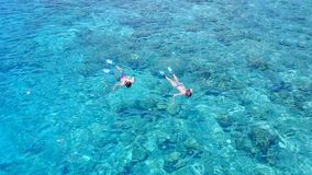 Aerial flying drone view of Maldives white sandy beach 2 people young couple man woman snorkeling swimming diving Stock Images