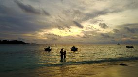 Aerial flying drone view of Maldives white sandy beach 2 people young couple man woman romantic love sunset Royalty Free Stock Images