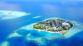 Aerial flying drone view of Maldives white sandy beach on sunny tropical paradise island with aqua blue sky sea Stock Photo