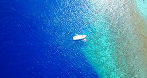 Aerial flying drone view of Maldives white sandy beach on sunny tropical paradise island with aqua blue sky sea. Water ocean 4k boat sailing stock video