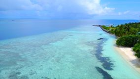 P02312 Aerial flying drone view of Maldives white sandy beach on sunny tropical paradise island with aqua blue sky sea Stock Photos
