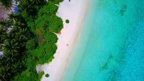 P02497 Aerial flying drone view of Maldives white sandy beach on sunny tropical paradise island with aqua blue sky sea Stock Photo