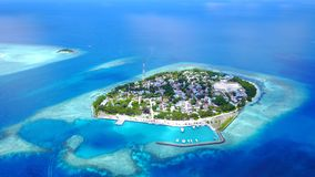 P02338 Aerial flying drone view of Maldives white sandy beach on sunny tropical paradise island with aqua blue sky sea Stock Photo